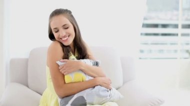 Young woman relaxing on her couch smiling at camera — Stock Video