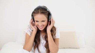Jonge vrouw luisteren naar muziek en dansen op haar bed — Stockvideo