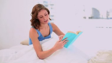Pleased woman reading a book sitting in her bed — Stock Video
