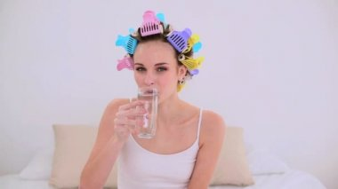 Young model in hair rollers drinking glass of water — Stock Video
