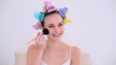 Young model in hair rollers putting make up on her face — Stock Video