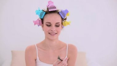Young model in hair rollers brushing her eyebrows — Stock Video