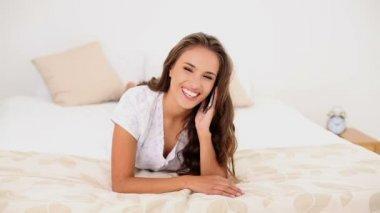 девушка разговаривает на ее телефон, лежащий на ее кровати — Стоковое видео