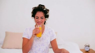 Joyful woman in hair curlers enjoying orange juice — Stock Video
