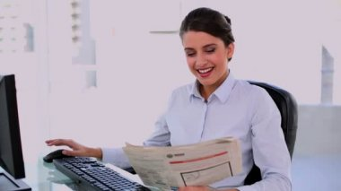 Thoughtful beautiful businesswoman using computer while reading newspaper — Stock Video