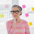 Thoughtful woman with glasses in creative office — Stock Photo