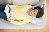 Cheerful casual brunette in yellow cardigan reading a book — Stock Photo