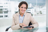 Smiling businesswoman using calculator — Stock Photo