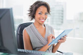 Beautiful businesswoman using her tablet pc and smiling at camera — Stock Photo