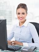Smiling young businesswoman sitting in front of computer — Stock Photo