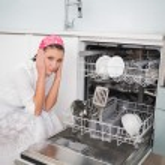 Anxious charming woman sitting next to dish washer — Stock Photo