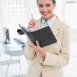 Pleased smart businesswoman filling an agenda — Stock Photo #33401207