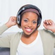 Dancing woman listening to music with headphones while looking at camera — Stock Photo