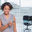Smiling woman standing in her office and using her phone — Stock Photo #33402463