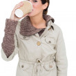 Content cute brunette in winter fashion drinking from disposable cup — Stock Photo #33403103