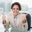 Happy businesswoman showing thumbs up at her desk — Stock Photo #33404451