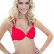 Openly smiling blonde model posing with hands on hips in red bikini — Stock Photo