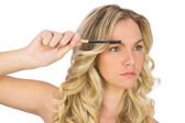 Thoughtful curly haired blonde using eyebrow brush — Stock Photo