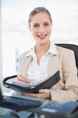 Smiling blonde businesswoman holding datebook — Stock Photo