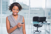 Smiling woman standing in her office and using her phone — Stock Photo