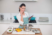 Happy gorgeous woman wearing apron using tablet — Stock Photo