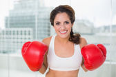 Sporty cheery brunette wearing boxing gloves — Stock Photo