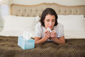 Casual pretty woman sneezing in a tissue — Stockfoto