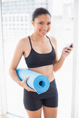 Cheerful model in sportswear carrying an exercise mat and a mobile phone — Foto de Stock