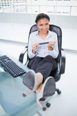 Cheerful young businesswoman filing her nails while sitting at her desk — Stock Photo