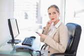 Thoughtful blonde businesswoman texting — Stock Photo