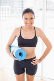 Lovely model in sportswear carrying a blue exercise mat — Stock Photo