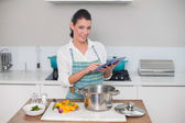 Woman wearing apron using tablet — Stock Photo