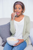 Cheerful attractive woman eating popcorn — Stock Photo
