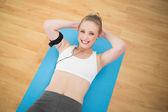 Sportif sarışın müzik dinleme ve egzersiz gülümseyen — Stok fotoğraf