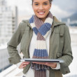 Portait of smiling woman standing outside and holding laptop — Stock Photo