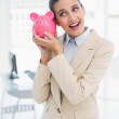 Surprised smart businesswoman shaking a piggy bank — Stock Photo