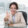 Cheerful businesswoman showing thumb up at her desk — Stock Photo