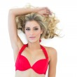 Attractive blonde model wearing red bikini posing with arm over head — Stock Photo #33416413