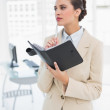 Thoughtful smart businesswoman filling an agenda — Stock Photo