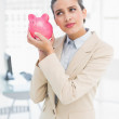 Frowning smart businesswoman shaking a piggy bank — Stock Photo