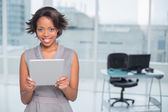 Smiling businesswoman standing in her office and holding tablet — Stock Photo