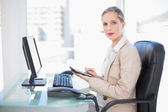 Side view of blonde businesswoman using calculator — Stock Photo