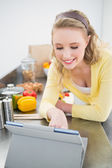 Smiling cute blonde looking at tablet — Stock Photo