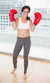 Sporty cheerful brunette wearing boxing gloves — Stock Photo