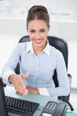 Smiling brunette businesswoman shaking hands — Stock Photo