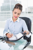 Businesswoman writing in a diary — Stock Photo