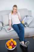 Casual smiling blonde phoning and using laptop — Stock Photo