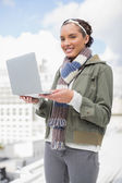 Happy woman standing outside and holding laptop — Stock Photo