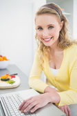 Smiling pretty blonde using laptop — Stock Photo