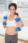 Sporty brunette lifting dumbbells — Stock Photo